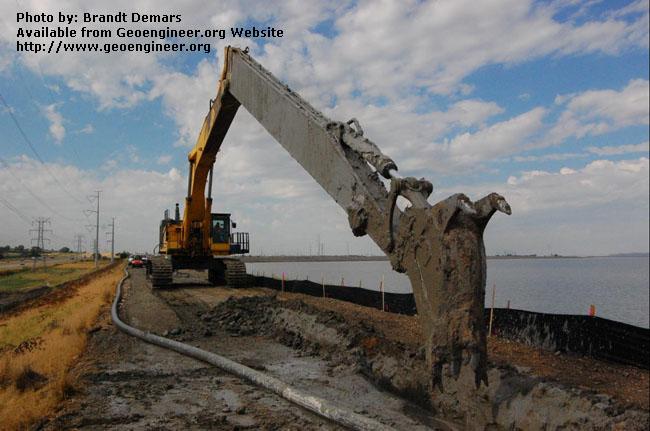 Title: The Komatsu PC1250 excavates a 40-foot section of CB wall<br>Title: D-526-418-5128 a?? The Komatsu PC1250 excavates a 40-foot section of CB wall near Station 732+00.  Donated by: Jeffrey A. Farrar Date: July 22, 2008