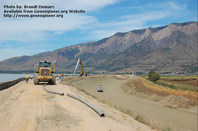 Title: The PC1250 excavator is walked along the dike towards a new heading.<br>Title: D-526-418-5319 a?? The PC1250 excavator is walked along the dike (Station 625+00) towards a new heading. The HDPE slurry supply pipeline is being fused on the dama??s crest, and the new batch plant can be seen in the far background.  Donated by: Jeffrey A. Farrar Date: August 19, 2008