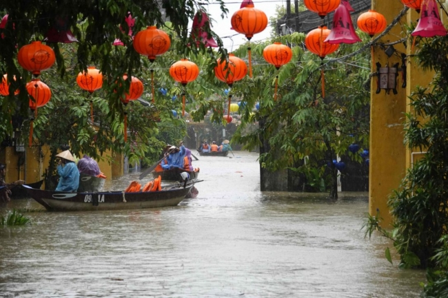 Residents are transported by boats through floodwaters in the tourist town of Hoi An on Sunday.