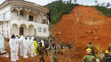 Rescue teams and soldiers operate near a mudslide site and damaged building near Freetown on August 15, 2017.