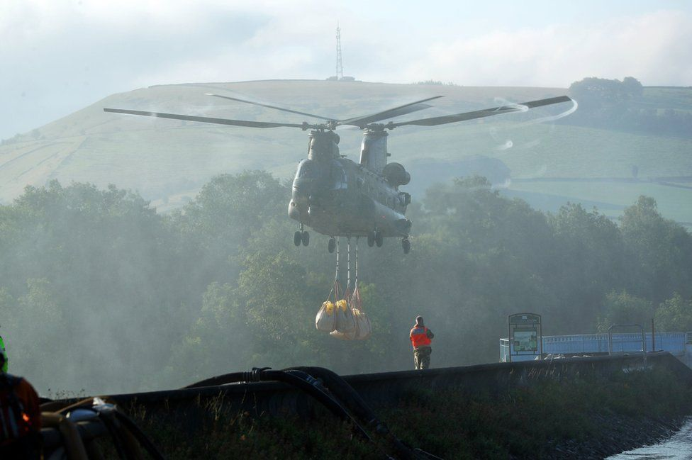 RAF helicopter dropping aggregates to reinforce the damaged section of the dam