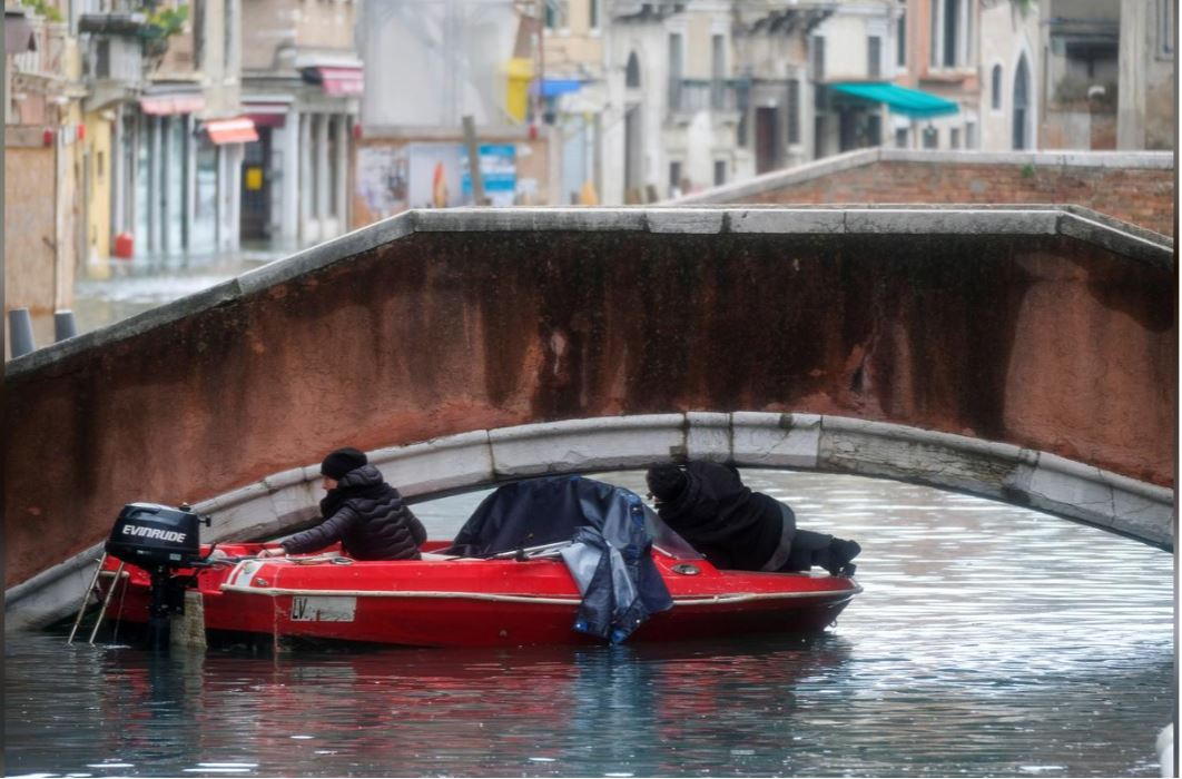 A boat trying to pass under a bridge in Venice